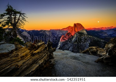 A full moon rises behind iconic Half Dome at sunset from Glacier Point in Yosemite National Park, California. - stock photo