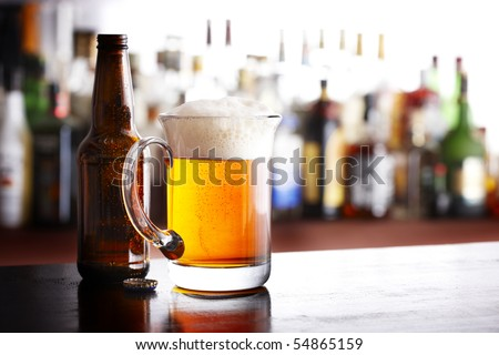 A full mug of beer with bottle and cap shot in bar - stock photo