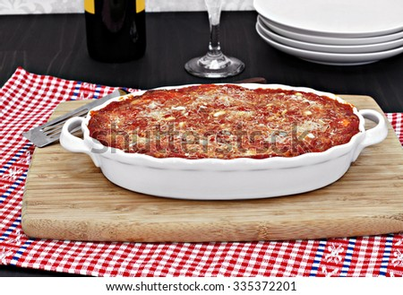 A full oval white baking pan of baked eggplant or lasagna.  Tomato parmesan topping. - stock photo