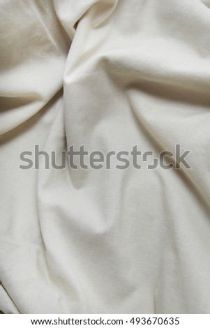 A full page of scrunched white cotton fabric background texture