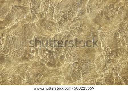 A full page of shallow sea water rippling over a yellow sandy beach background texture