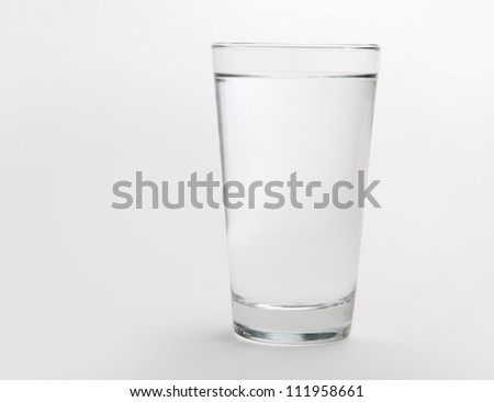 A full pint glass of water on a neutral background. Glass has no reflections and is evenly lit.