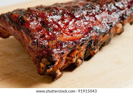 a full rack barbecue pork back ribs with sauce on a cutting board with a white background