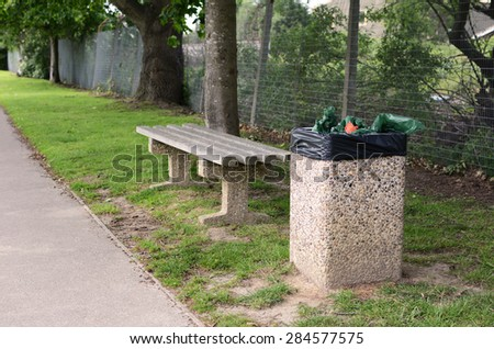 A full rubbish bin makes an empty bench an unwelcoming place to rest - stock photo