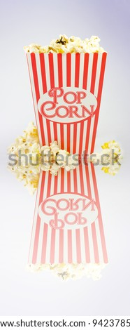 A full to overflowing iconic red and white striped popcorn carton on white with reflection - stock photo