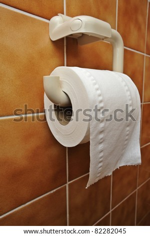 A full toilet roll on a tiled wall - stock photo
