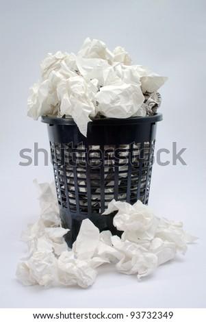 a full trash basket on white background - stock photo