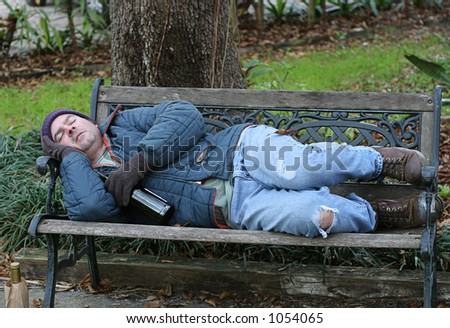 A full view of a homeless man asleep on a park bench with his wine bottle. - stock photo