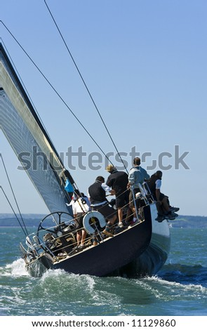 A fully crewed racing yacht catching the wind - stock photo