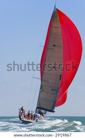 A fully crewed racing yacht with a red spinnaker catching the wind and leaving a big wake - stock photo