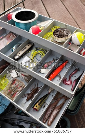 A fully stock fisherman's tackle box fully stocked with lures and gear for fishing. - stock photo