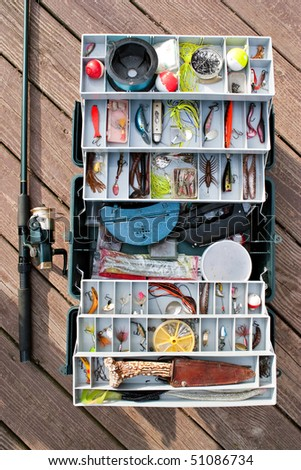 A fully stock fisherman's tackle box rod and reel ready for a long day of fishing. - stock photo
