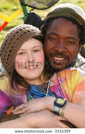 a fun colorful multicultural couple (black man and white girl) enjoying spring sun on the grass in the park. Part of a bicycle visible in the background - stock photo
