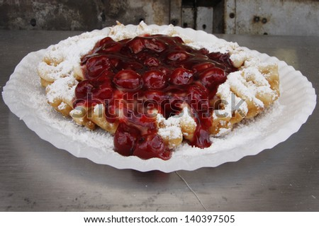 A funnel cake topped with sugar and cherry syrup - stock photo