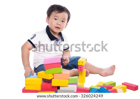 a funny boy is playing with toy blocks. Isolated on a white background