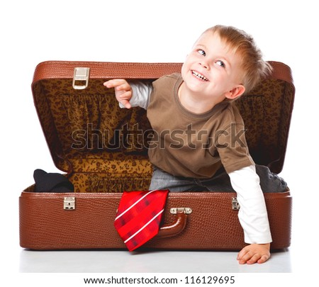 A funny boy with sombrero is sitting in the suitcase. Isolated on a white background - stock photo