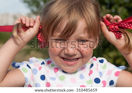 A funny cute outdoor close up portrait of a smiling little girl presenting Pippi Longstocking   - stock photo