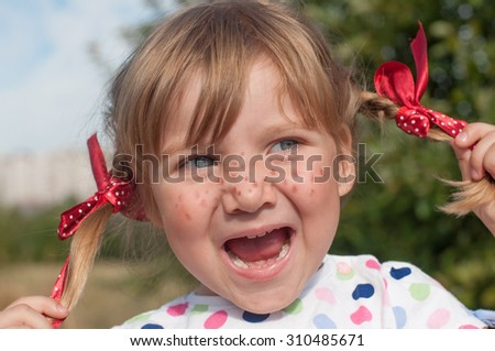 A funny cute outdoor close up portrait of a smiling little girl presenting Pippi Longstocking  and making faces   - stock photo
