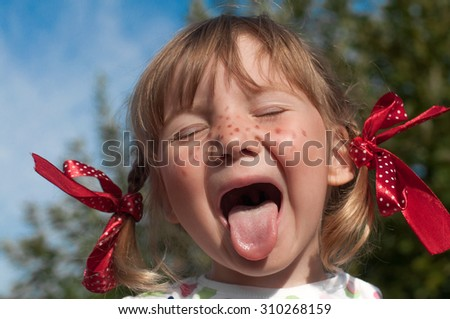 A funny cute outdoor portrait of a little girl presenting Pippi Longstocking and showing out out her tongue  - stock photo