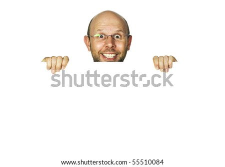 A funny happy smiling man holding a white sign or looking up from behind white wall - stock photo