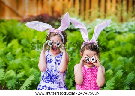 A funny portrait of two girls having fun on Easter wearing bunny ears and holding up silly eyes made from eggs outside in a garden during the spring season.  Part of a series.   - stock photo