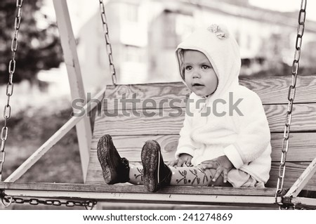 a funny toddler girl on the swing - stock photo