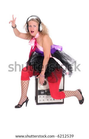 a funny woman in headphones sitting on old tape recorder - stock photo