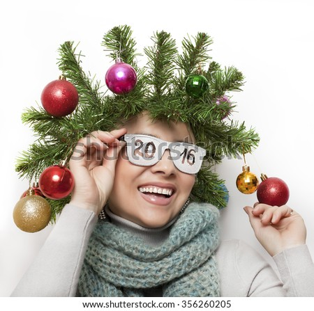 A funny woman with a wreath from the Christmas tree on his head and wearing glasses with the words 2016 - stock photo