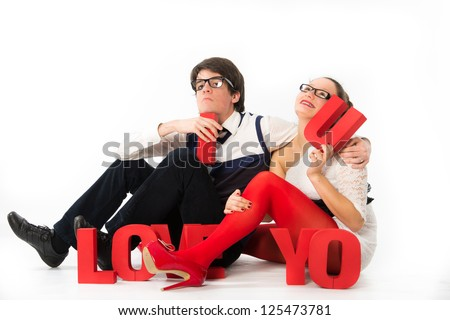 A funny young couple holding red letters love celebrating Valentine\s Day - stock photo