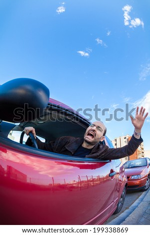 A furious driver in a traffic jam, leaning out the car's window and shouting.