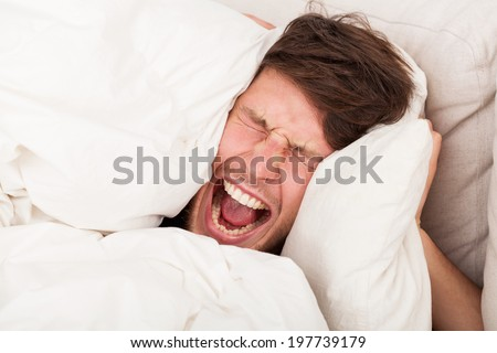 A furious man reluctant to wake up in the morning - stock photo