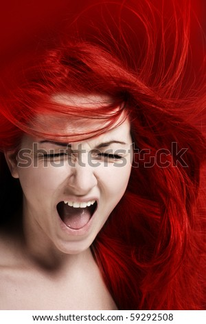 A furious young woman with her hair red like fire. - stock photo