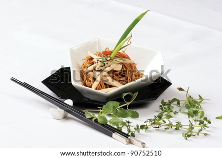 A fusion chinese fried noodle served in dark soy sauce and fresh leaf. - stock photo