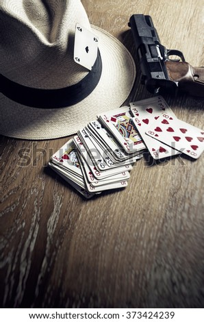 A gambling card set next to a gangster hat and a handgun on a wooden table