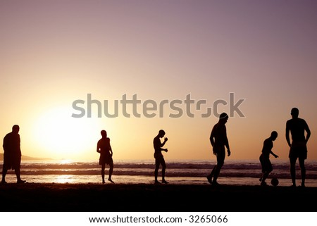 A game of football on the beach at sunset - stock photo