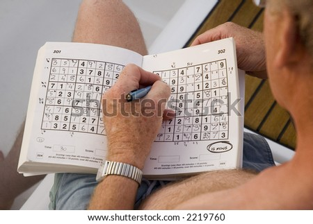 A game of Sudoku on a sailing holiday in the Mediterranean - stock photo