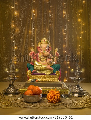 A Ganesha idol in elaborate Indian pooja set up and decoration - stock photo