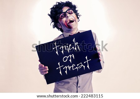a gap-toothed zombie showing a black signboard with the text trick or treat written in it, with a retro effect - stock photo