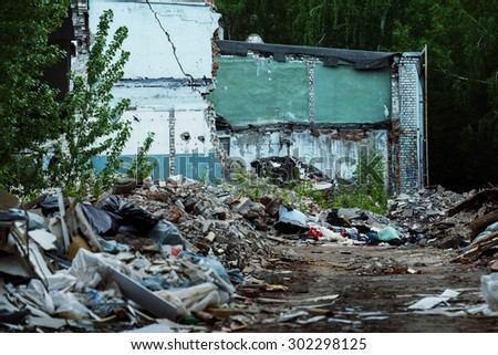 A garbage dump and a building with ruined brick walls at background. Concept of disaster, war. Retreat for homeless. - stock photo