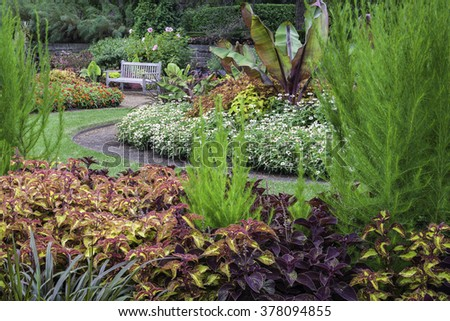 A garden bench invites visitors to Cantigny Park in Wheaton, Illinois, to relax and admire the amazing planting beds filled with colorful summer botanicals. - stock photo