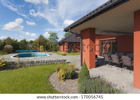 A garden of a luxurious house with a swimming pool - stock photo