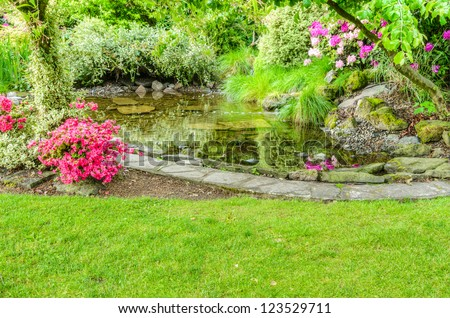 A garden scene with blooming azaleas and a fish pond