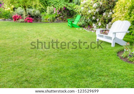 A garden scene with green lawn and benches - stock photo