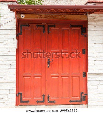 A garden wooden door with hardware from wrought iron and lined with stone columns - stock photo