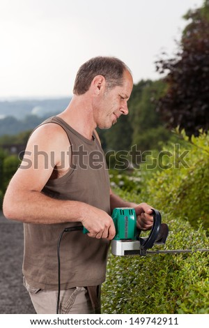 A Gardener is working in his garden at a sunny day.