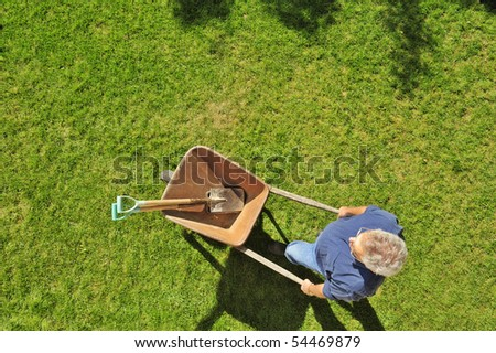 A gardener setting off to work with his wheelbarrow and tools, taken from a high viewpoint. Space for text across top of image - stock photo
