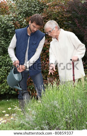 A gardener watering flowers in a garden and an elderly lady making comments as she watches him. - stock photo