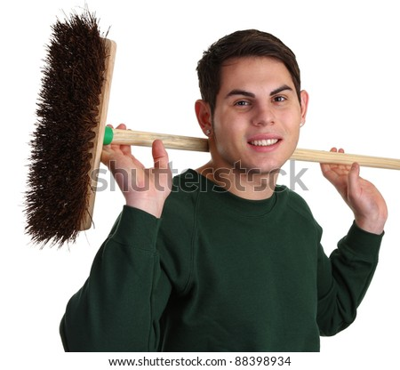 A gardener with a green jacket with a wooden broom - stock photo