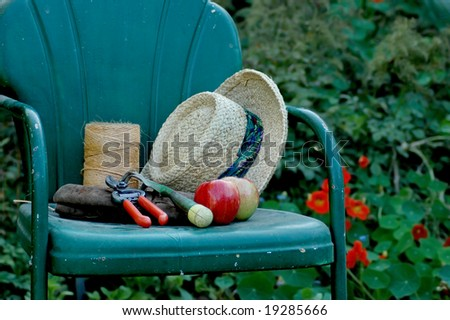 A gardening hat and tools rest on a chair. - stock photo