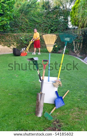 A gardner mows a lawn and prepares to conduct other gardening work - stock photo